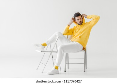 handsome young man in yellow hoodie putting on hood while sitting on chairs on white