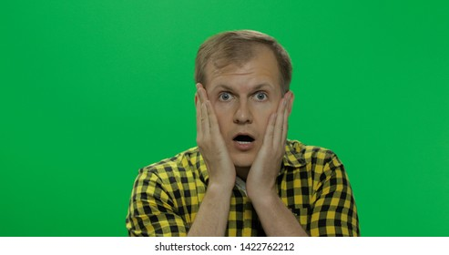 Handsome young man in the yellow shirt desperate and sad, is pessimistic and melancholy on the chroma key background. Green screen.