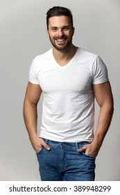 Handsome young man,boy,posing in white t shirt and jeans with hands in pockets