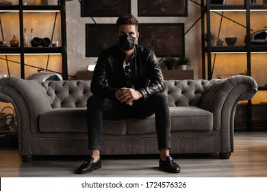 Handsome young manin black mask. Fashionable man in leather jacket standing and looking at window.