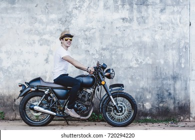 Handsome young men with black color classic motobike(motorcycle) on cement background.
