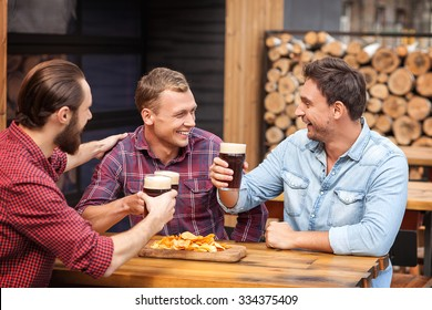 Handsome young men are resting and sitting in bar. They are talking and smiling. The friends are drinking beer and eating chips