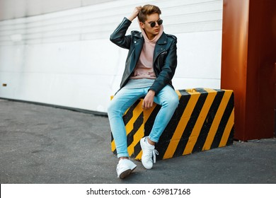 Handsome young model of a man wearing sunglasses in a black leather jacket, a pink sweatshirt, blue jeans and white shoes sits on a black-and-yellow slab