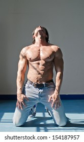 Handsome young muscle man shirtless kneeling on the floor, holding head up, wearing jeans