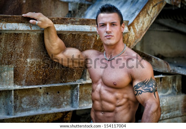 Handsome young muscle man shirtless with hand on rusty metal structure, looking in camera