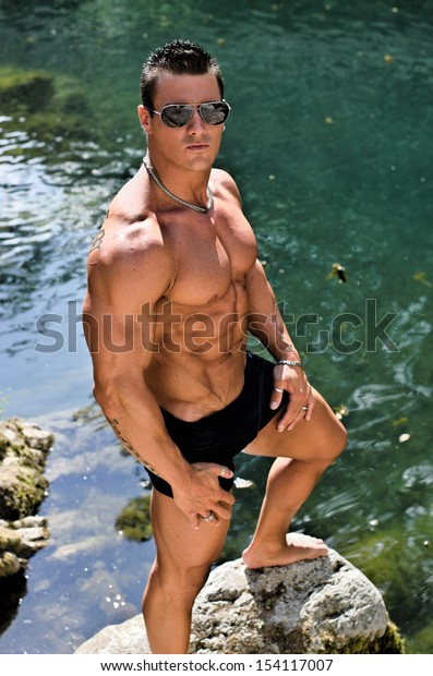 Handsome young muscle man standing in water pond shirtless with sunglasses