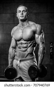Handsome young muscular Caucasian man of model appearance working out training pumping up abdominal muscles abs sixpacks in the gym fitness and bodybuilding concept