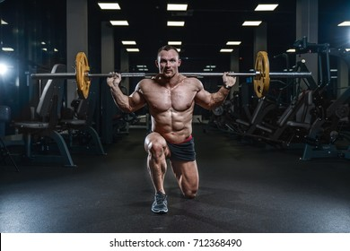 Handsome young muscular Caucasian man of model appearance working out in the gym training legs quadriceps and hamstrings on machines and with a barbell pumping up fitness and bodybuilding concept