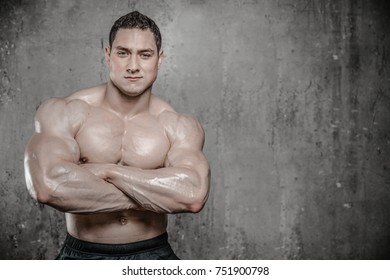 Handsome young muscular caucasian man of model appearance posing on grey background gaining weight pumping up muscles and poses fitness and bodybuilding concept