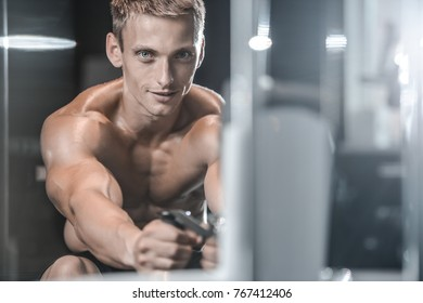 Handsome young muscular Caucasian man of model appearance working out training pumping up back lats muscles in the gym gaining weight on machines posing fitness and bodybuilding concept