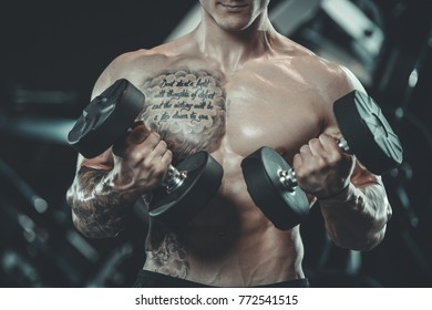 Handsome young muscular Caucasian man of model appearance working out training in the gym gaining weight pumping up muscles and poses fitness and bodybuilding concept