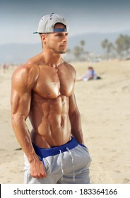Handsome young muscular male model on the beach enjoying summer