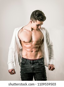 Handsome young muscular man shirtless wearing jeans, taking off white shirt on naked muscle torso, on light background in studio shot