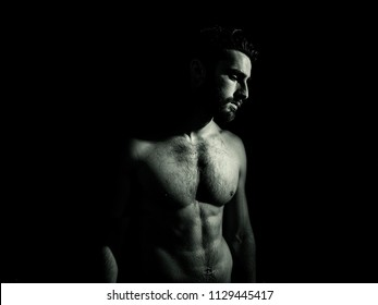 Handsome young muscular man shirtless, on black background in studio shot