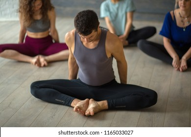 Handsome young muscular man, yogi teacher conducting yoga to caucasian women, sitting in baddha konasana, butterfly pose. Group training. Healthy lifestyle concept.