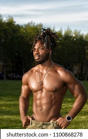 Handsome young muscular shirtless African American man standing in the park lit by afternoon sun.