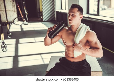 Handsome young muscular sportsman is drinking water while resting after workout in gym