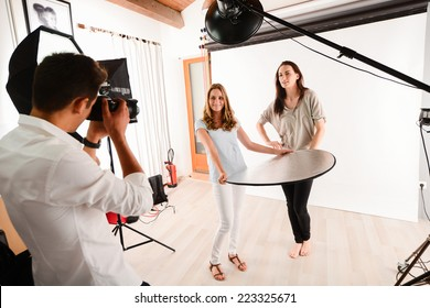 handsome young photographer taking pictures of a beautiful girl  fashion model