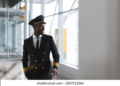 handsome young pilot with luggage at airport looking away