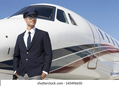 Handsome young pilot standing by private airplane