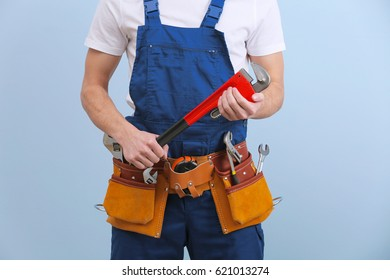 Handsome young plumber with tools on color background