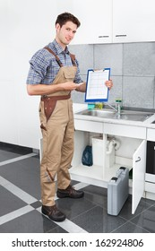 Handsome Young Plumber Writing On Clipboard With Pen In Kitchen Room