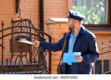 Joli jeune facteur mettant une lettre dans une boîte aux lettres à l'extérieur