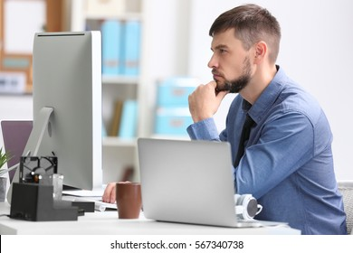 Handsome young programmer working in office