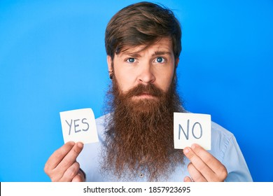 Handsome young red head man with long beard holding yes and no reminder relaxed with serious expression on face. simple and natural looking at the camera.