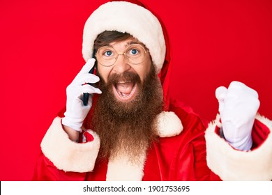 Handsome young red head man with long beard wearing santa claus costume talking on the phone screaming proud, celebrating victory and success very excited with raised arms