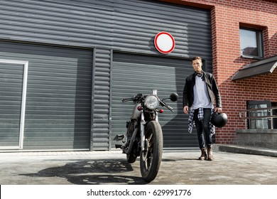 Handsome young rider guy in black biker jacket and jeans go to his classic style cafe racer motorcycle industrial gates as background. Bike custom made in vintage garage. Brutal fun urban lifestyle.