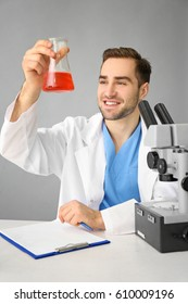 Handsome young scientist testing samples, on light background
