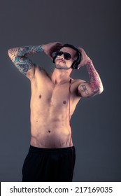 handsome young shirtless latin tattooed man holding headphones on his head posing