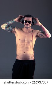 handsome young shirtless tattooed man holding headphones on his head posing