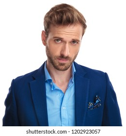 handsome young smart casual man with a smug look posing on white background