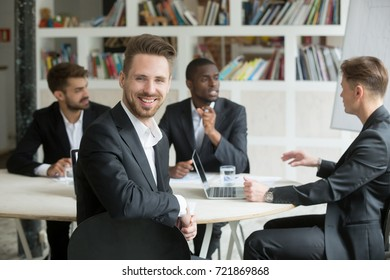 Handsome young smiling businessman looks at camera during business meeting. Team of male corporate colleagues on background, Friendly male executive, successful company representative, CEO or manager