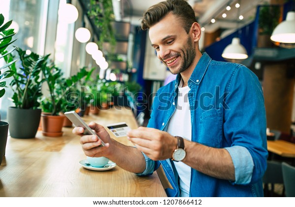 Handsome young smiling man with credit card and phone in hands doing purchases during online shopping