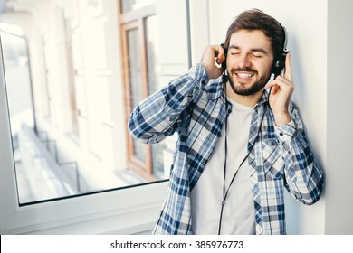 Handsome young smiling man listening to music in front of window