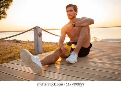 Handsome young smiling sportsman sitting and holding water bottle outdoors