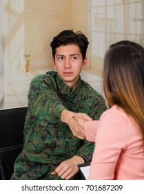 Handsome young soldier wearing uniform, with a woman therapist shaking hands for the therapy in a medical health center, in a office background