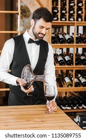 handsome young sommelier pouring wine from decanter at wine store