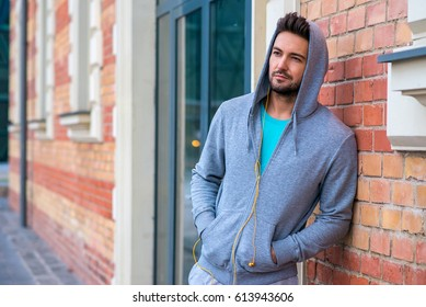 A handsome young sportsman standing next to a brickwork with his hood on