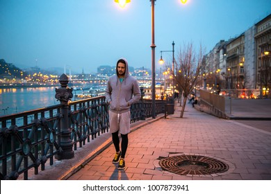 A handsome young sportsman walking on the street in the city lights at night