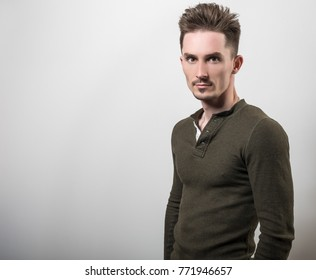 Handsome young sporty man in green t-shirt pose against gray studio background.