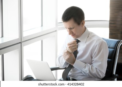 Handsome young stressed businessman sitting in his office using laptop. Caucasian businessperson touching his aching wrist with pained expression after working on pc