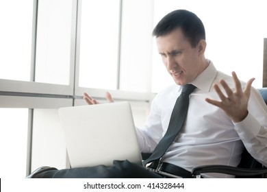 Handsome young stressed businessman sitting in his office using laptop. Caucasian businessperson looking at screen with irritated expression, made mistake or annoyed by work. Negative human emotions