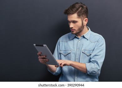 Handsome young student in jeans shirt is using a tablet, standing against blackboard