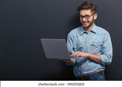 Handsome young student in jeans shirt and eyeglasses is using a laptop and smiling, standing against blackboard