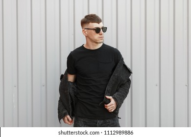 Handsome young stylish man with sunglasses in a denim fashion jacket and a black t-shirt poses near the gray wall
