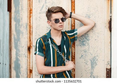 handsome young stylish man with sunglasses in a fashion beach shirt near a vintage wall